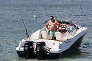 A white man stands with his hands on his hips in his power boat in the English Channel just outside Folkestone Harbour, Kent, England, United Kingdom. He has set up a fishing rod of the back side of the boat.