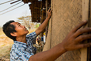 """01 MARCH 2014 - MAE SOT, TAK, THAILAND:  A Burmese man puts a new exterior wall on his home in a small Burmese community in the forest a few kilometers north of Mae Sot. The new wall is a rattan mat. Mae Sot, on the Thai-Myanmer (Burma) border, has a very large population of Burmese migrants. Some are refugees who left Myanmar to escape civil unrest and political persecution, others are """"economic refugees"""" who came to Thailand looking for work and better opportunities.   PHOTO BY JACK KURTZ"""