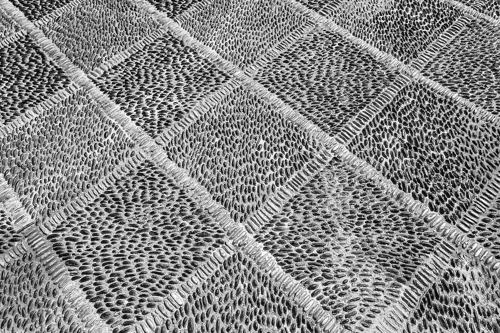 Black and white stones in a grid pattern on a walkway in Greece are inlaid by hand