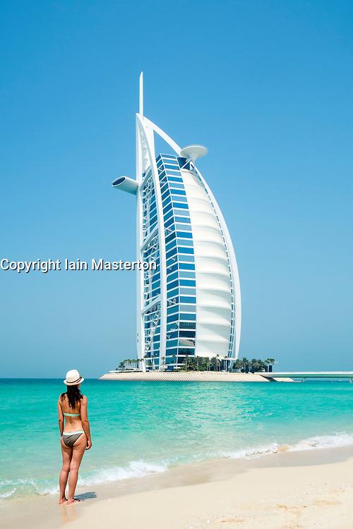 Woman walking on beach at Burj Al Arab luxury hotel in Dubai United Arab Emirates