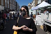 Young Asian woman wearing two pairs of glasses and a face mask on Portobello Road in Notting Hill, West London, England, United Kingdom. People enjoying a sunny day out hanging out at the famous Sunday market, when the antique stalls line the street.  Portobello Market is the worlds largest antiques market with over 1,000 dealers selling every kind of antique and collectible. Visitors flock from all over the world to walk along one of Londons best loved streets.