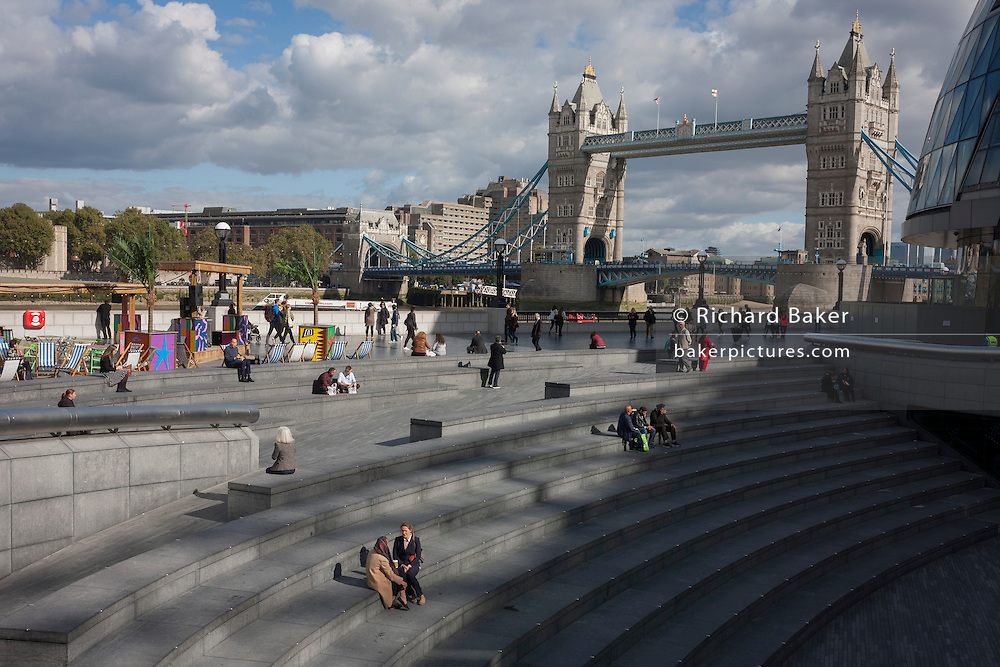 Lunchtime women talk with a background panorama looking north from More London in Southwark, towards Tower Bridge.