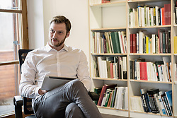 Mid adult businessman using digital tablet in an office and thinking, Bavaria, Germany