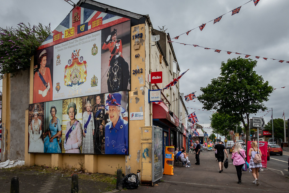 Mural celebrating 60 years of the Queen' reign. Flags flying ahead of the famous Orange March, West Belfast, NI, 2021