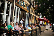 """SHOT 8/28/09 7:13:24 PM - Happy hour on a summer evening at the Goosetown Tavern and Mezcal on Colfax Avenue in Denver, Co. Colfax Avenue is the main street that runs east and west through the Denver-Aurora metropolitan area in Colorado. As U.S. Highway 40, it was one of two principal highways serving Denver before the Interstate Highway System was constructed. In the local street system, it lies 15 blocks north of the zero point (Ellsworth Avenue, one block south of 1st Avenue). For that reason it would normally be known as """"15th Avenue"""" but the street was named for the 19th-century politician Schuyler Colfax. On the east it passes through the city of Aurora, then Denver, and on the west, through Lakewood and the southern part of Golden. Colloquially, the arterial is referred to simply as """"Colfax"""", a name that has become associated with prostitution, crime, and a dense concentration of liquor stores and inexpensive bars. Playboy magazine once called Colfax """"the longest, wickedest street in America."""" However, such activities are actually isolated to short stretches of the 26-mile (42 km) length of the street. Periodically, Colfax undergoes redevelopment by the municipalities along its course that bring in new housing, trendy businesses and restaurants. Some say that these new developments detract from the character of Colfax, while others worry that they cause gentrification and bring increased traffic to the area. (Photo by Marc Piscotty / © 2009)"""