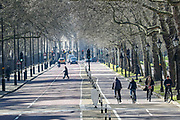 People are seen walking and cycling through St James's Park in London, Monday, March 23, 2020. The British government is encouraging people to practice social distancing to help prohibit the spread of Coronavirus, further restrictions may be imposed if the public do not adhere to their advice. (Photo/Vudi Xhymshiti)