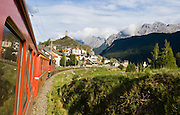 """A Swiss train approaches a medieval castle in Ardez, Lower Engadine, Grison Alps, Switzerland, Europe. The Swiss valley of Engadine translates as the """"garden of the En (or Inn) River"""" (Engadin in German, Engiadina in Romansh, Engadina in Italian)."""