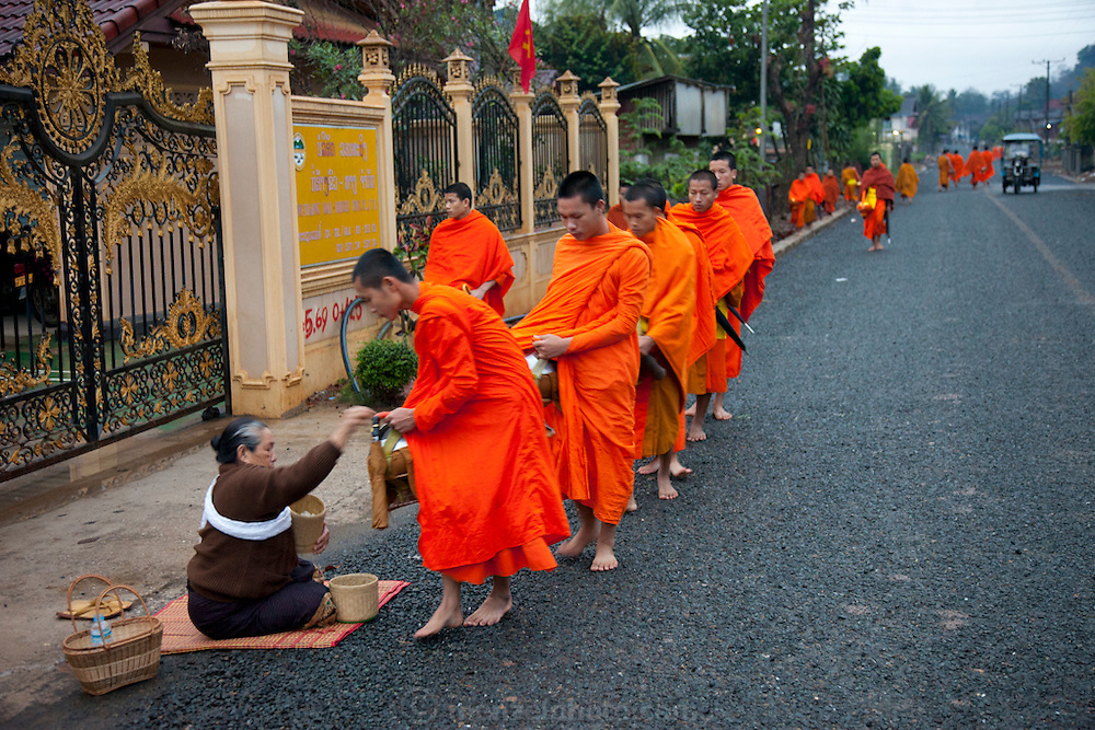"""In Ban Phan Luang, across the Nam Khan River from Luang Prabang, Laos. Every morning at dawn, Buddhist monks walk down the streets collecting food alms from devout, kneeling Bhddhists, and some tourists. They then return to their temples (also known as """"wats"""") and eat together. This procession is called Tak Bat, or Making Merit."""