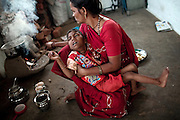 Poona Bai, 40, is holding her son Raj, 7, a child presenting a severe neurological disorder, while making Indian chai tea for her family in the impoverished Oriya Basti colony, Bhopal, Madhya Pradesh, India, near the abandoned Union Carbide (now DOW Chemical) industrial complex.