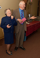 Chairperson Joyce Ringleb and Councilor Raymond Burton share a laugh while welcoming families to the Hands Across The Table dinner at St. James Episcopal Church Tuesday evening.    (Karen Bobotas/for the Laconia Daily Sun)