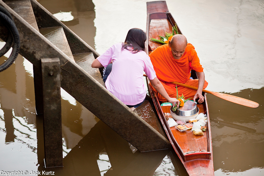 """10 JULY 2011 - AMPHAWA, SAMUT SONGKRAM, THAILAND:  A Buddhist monk from Wat Amphawan Chetiyaram in Amphawa, Thailand, about 90 minutes south of Bangkok, collects alms from people """"making merit"""" on the main canal during his alms round. Most of the monks from the temple use boats to go from house to house on their alms rounds. The Thai countryside south of Bangkok is crisscrossed with canals, some large enough to accommodate small commercial boats and small barges, some barely large enough for a small canoe. People who live near the canals use them for everything from domestic water to transportation and fishing. Some, like the canals in Amphawa and nearby Damnoensaduak (also spelled Damnoen Saduak) are also relatively famous for their """"floating markets"""" where vendors set up their canoes and boats as floating shops.      PHOTO BY JACK KURTZ"""