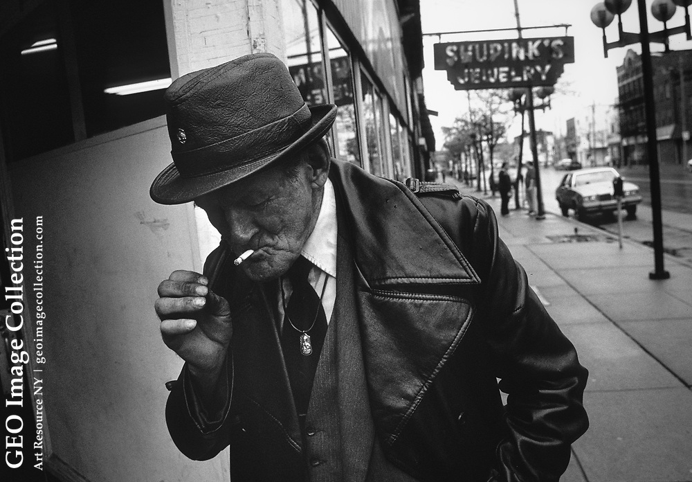 Old man smoking a cigarette enters Rainbow Kitchen, a charity organization in Homestead neighborhood of Pittsburgh. Rainbow Kitchen feeds hungry people in this bleak and depressed town.