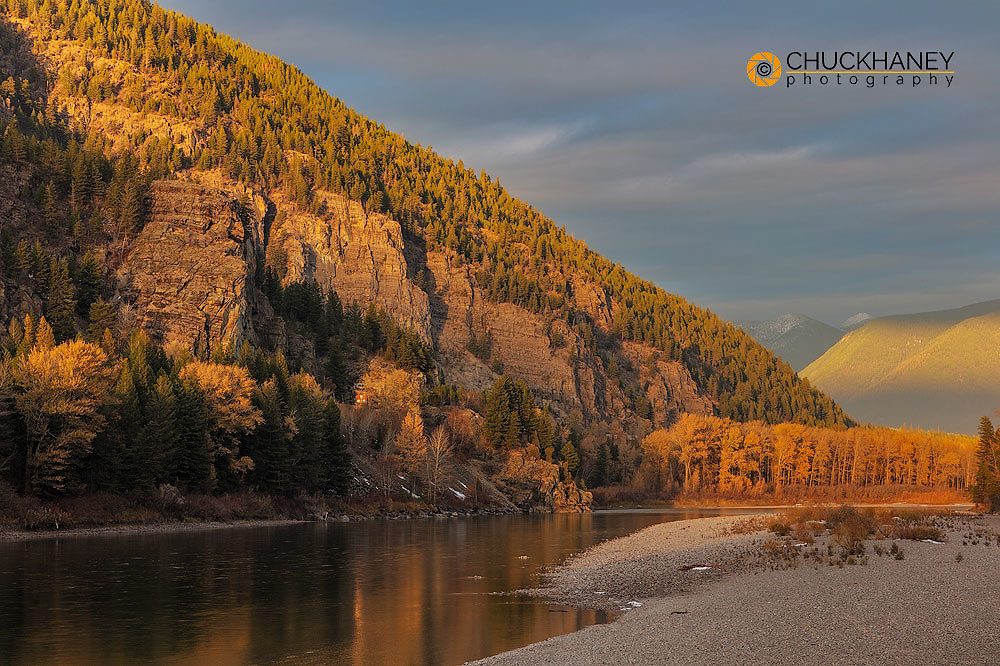 Late light falls on the Flathead River as Freight Train emerges from tunnel in Bad Rock Canyon near Coumbia Falls, Montana, USA