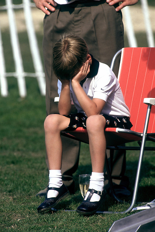 Prince William sits looking fed up during a polo match at the Guards Polo Club, Windsor in July 1989. photograph by Jayne Fincher