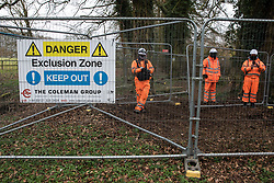 Wendover, UK. 18th March, 2021. HS2 security guards stand behind fencing erected to facilitate the demolition of a large residential house and the felling of woodland for the HS2 high-speed rail link.