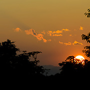 The sun sets on the horizon past silhouetted trees in Luang Namtha province in Northern Laos.