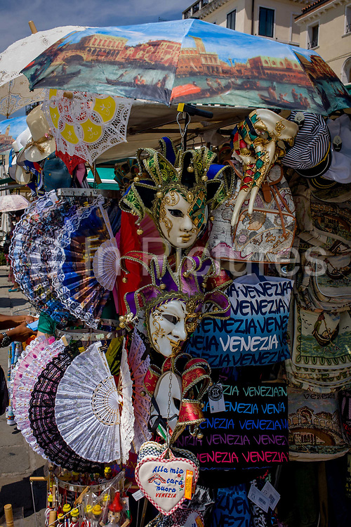 Tourist souvenirs on sale outside the Doge's Palace in Piazza San Marco, Venice, Italy. The wide expanse of Piazza San Marco is in the heart of Venice and where, for most daylight hours, the pavement is crowded with humanity as the influx of tourists who, in their own way, flood the narrow streets with sun-shading umbrellas and the smaller canals with gondolas. Venice attracts 22-million visitors each year (for a city of only about 60,000 residents) while the cultural protection organisation, Italian Nostra, warns that Venice can only accommodate about Venice attracts 22-million visitors each year (for a city of only about 60,000 residents) while the cultural protection organisation, Italian Nostra, warns that Venice can only accommodate about 33,000 visitors per day.