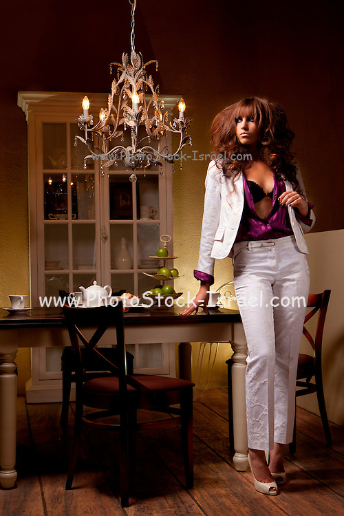 Woman in trouser suit stands by her dining room table