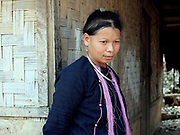 A Lanten ethnic minority woman wearing traditional indigo-dyed cotton clothing outside her home, Ban Houey Liey, Luang Namtha province, Lao PDR. The Lanten or Yao Mun are a small but distinctive group of the Yao ethnic minority residing in northern Laos, Vietnam and China. Maintaining a strong cultural identity, they are easily recognised by their hand woven, indigo dyed attire. Unlike many other ethnic groups who have relinquished their traditional dress, each Mun family still cultivates cotton and indigo for spinning, weaving, dyeing and sewing into clothing. One of the most ethnically diverse countries in Southeast Asia, Laos has 49 officially recognised ethnic groups although there are many more self-identified and sub groups. These groups are distinguished by their own customs, beliefs and rituals.