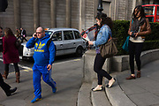 "A man wearing a bright Adidas tracksuit-type of sports clothing walks and talks passing the pillars of the Bank of England. On an otherwise dull street minus strong colour elsewhere, the man wears the bright blue from head top foot including the 3 stripes of the sports clothing brand known throughout the world. Adolf Dassler, following the split of Gebrüder Dassler Schuhfabrik between him and his older brother Rudolf, founded Adidas in 1948. Rudolf later established Puma, which was the early rival of Adidas. Registered in 1949, Adidas is currently based in Herzogenaurach, Germany, along with Puma. The company's clothing and shoe designs typically feature three parallel bars, and the same motif is incorporated into Adidas's current official logo. The ""Three Stripes"" were bought from the Finnish sport company Karhu Sports in 1951."