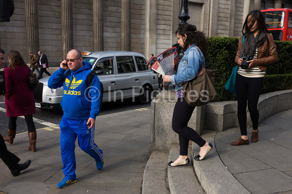 """A man wearing a bright Adidas tracksuit-type of sports clothing walks and talks passing the pillars of the Bank of England. On an otherwise dull street minus strong colour elsewhere, the man wears the bright blue from head top foot including the 3 stripes of the sports clothing brand known throughout the world. Adolf Dassler, following the split of Gebrüder Dassler Schuhfabrik between him and his older brother Rudolf, founded Adidas in 1948. Rudolf later established Puma, which was the early rival of Adidas. Registered in 1949, Adidas is currently based in Herzogenaurach, Germany, along with Puma. The company's clothing and shoe designs typically feature three parallel bars, and the same motif is incorporated into Adidas's current official logo. The """"Three Stripes"""" were bought from the Finnish sport company Karhu Sports in 1951."""