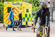 An ambulance on standby in the park is passed by a steady flow of people not staying home to protect the NHS and save lives - 'Battersea Park is much quieter as the weather is cooler and mixed with fairly heavy showers. The 'lockdown' continues for the Coronavirus (Covid 19) outbreak in London.