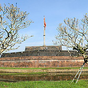 The citadel flag seen from across the moat at the Imperial City in Hue, Vietnam. A self-enclosed and fortified palace, the complex includes the Purple Forbidden City, which was the inner sanctum of the imperial household, as well as temples, courtyards, gardens, and other buildings. Much of the Imperial City was damaged or destroyed during the Vietnam War. It is now designated as a UNESCO World Heritage site.