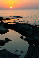 A silhouetted man fishes by the sea at sunset in Beirut, Lebanon