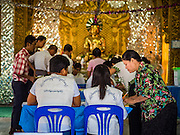 08 NOVEMBER 2015 - YANGON, MYANMAR:  A woman gets her ballot in her polling place in a Buddhist temple in North Okkalapa, a township outside central Yangon. The citizens of Myanmar went to the polls Sunday to vote in the most democratic elections since 1990. The National League for Democracy, (NLD) the party of Aung San Suu Kyi is widely expected to get the most votes in the election, but it is not certain if they will get enough votes to secure an outright victory. The polls opened at 6AM. In Yangon, some voters started lining up at 4AM and lines were reported to long in many polling stations in Myanmar's largest city.     PHOTO BY JACK KURTZ