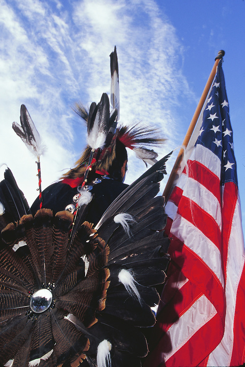 North America, United States, Washington, Seattle, Native American dancer with eagle feathers and American flag at annual Seafair powwow