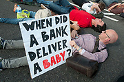 October 9th 2011. Blockade of Westminster Bridge organised by UK Uncut before the NHS bill goes before Parliament on October 12th. Protester holds a sign saying 'When did a bank deliver a baby'.