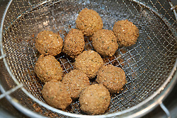 Middle East, Israel, Jerusalem,  falafel balls in fryer.  Falafel is made from ground chickpeas and/or fava beans. Falafel is usually served in a pita, which acts as a pocket,
