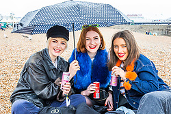 © Licensed to London News Pictures. 11/05/2019. Brighton, UK. London friends (LtoR) NICOLE BAYLEY, PHOEBE SCOTT and ALIESHA VIAN shelter from the rain under an umbrella. The girls are visiting Brighton as part of The Great Escape music festival and the Brighton Fringe Festival. Photo credit: Hugo Michiels/LNP