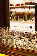 Glasses lined up backlit on a bar counter for a wine tasting. Restaurant L'Angle du Faubourg, Paris. Languedoc. France. Europe.