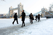 People walk to work on the south bank in front of Tower Bridge after snow has fallen overnight in London, England on February 28th, 2018. Freezing weather conditions dubbed the Beast from the East have brought snow and sub-zero temperatures to the UK.
