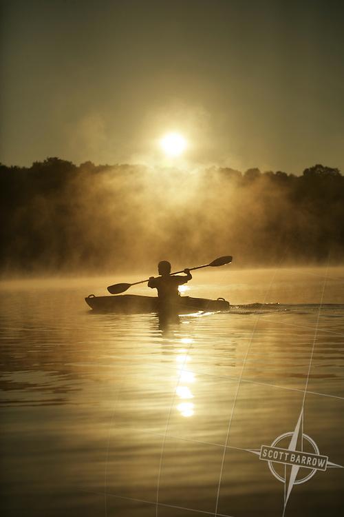 Kayak on a lake with sunrise fog.