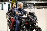 Een ouder stel zit samen op een Suzuki. In Utrecht vindt voor de 30e keer de Motorbeurs plaats. De jaarlijkse beurs trekt altijd veel bezoekers die op de nieuwe modellen motoren kunnen zitten. Daarnaast is er ook veel aandacht voor de accessoires. De motorrijder vergrijst, de gemiddelde leeftijd ligt boven de 45, in 2000 was dat nog 39.<br /> <br /> In Utrecht the 30th  Motorbeurs takes place. The annual trade event, always attracts many visitors who can try the new models. There is also a lot of attention to accessories. The motorcyclist ages, the average age is over 45, in 2000 it was 39.