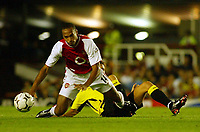 Photograph: Scott Heavey.<br />Arsenal v Aston Villa. FA Barclaycard Premiership match. 27/08/2003.<br />Thierry Henry goes down under the challenge from Peter Whittingham.
