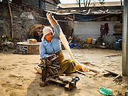01 MARCH 2017 - KHOKANA, NEPAL: A woman spins wool to make blankets in an informal IDP camp in Khokana. Her home was destroyed in the 2015 earthquake. Recovery seems to have barely begun nearly two years after the earthquake of 25 April 2015 that devastated Nepal. In some villages in the Kathmandu valley workers are working by hand to remove ruble and dig out destroyed buildings. About 9,000 people were killed and another 22,000 injured by the earthquake. The epicenter of the earthquake was east of the Gorka district.     PHOTO BY JACK KURTZ