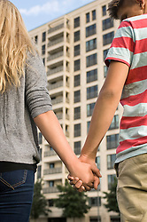 Teenage couple holding hands, close up