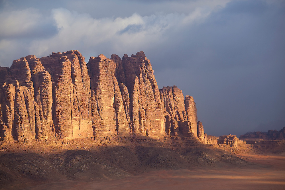 High sandstone cliffs at sunrise in Wadi Rum, Jordan.