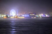 An atmospheric evening looking across the River Mersey to the Liverpool Waterfront. Fairground lights glow in the mist and reflect in the foreground waters. A night scene in Mersyside, England, UK.