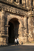 People passing through Porta Nigra, a large Roman city gate in Trier, Germany.