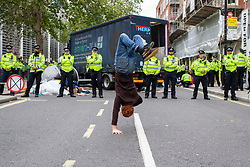 © Licensed to London News Pictures. 08/10/2019. London, UK. An Extinction Rebellion protester performs a hand stand in front of a police line outside the Home Office. Police continue to attempt to open roads in Westminster on the second day of the protest. Photo credit: George Cracknell Wright/LNP