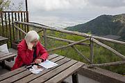 Lady reads magazine during visit to the Vesuvius volcano.
