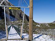 An Asian man walks across the Hooker Bluff suspension bridge on his way up the Hooker Valley Track, Aoraki/Mt. Cook National Park.