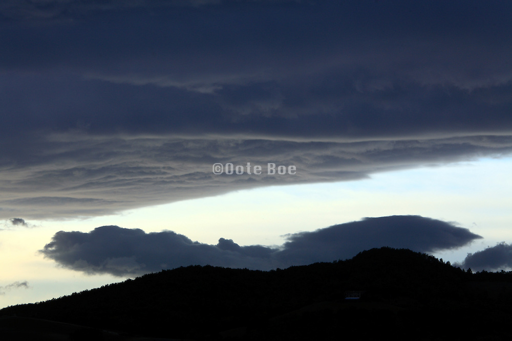 cloud formations above a silhouetted hilly landscape