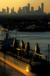 Tanker passing through the Port of Houston with the downtown Houston skyline on the horizon at sunrise.
