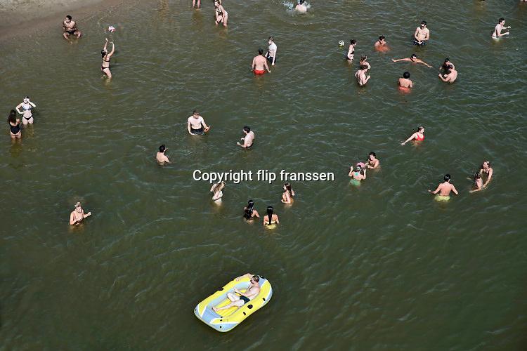 Nederland, nijmegen, 25-6-2019 Mensen trekken massaal naar de oevers van de waal en de spiegelwaal in het rivierpark aan de overkant van Nijmegen . De warmte, hoge temeratuur,  drijft mensen naar het water  . Het is verboden in de rivier te zwemmen vanwege de stroming het het drukke scheepvaartverkeer .  . Foto: ANP/ Hollandse Hoogte/ Flip Franssen