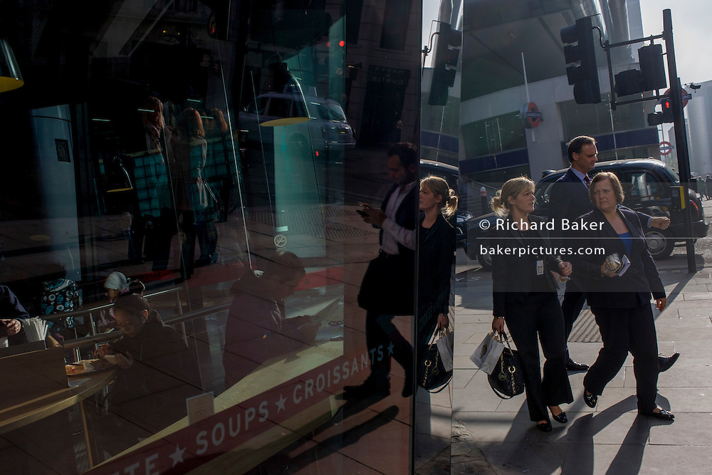 Reflected in a sandwich business window, pedestrians walk along Cannon Street in lunchtime sunshine in the City of London.